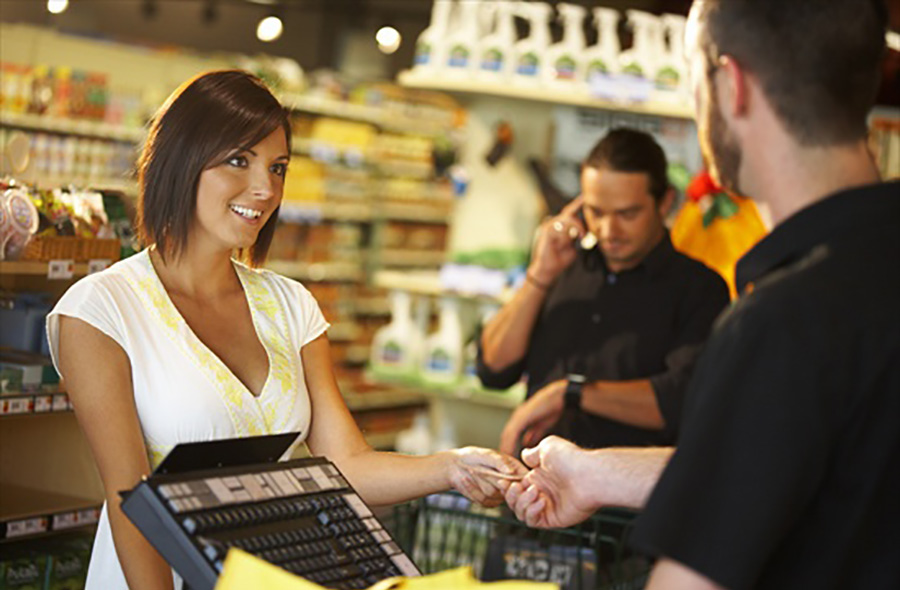 woman paying at cash register at store